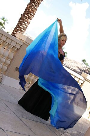 sexy blonde belly dancer making eye contact with viewer as her veil swirls behind her photo