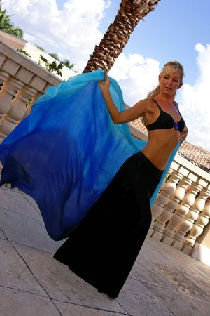 attractive blonde belly dancer in black skirt on balcony with silk veil with knee bent photo