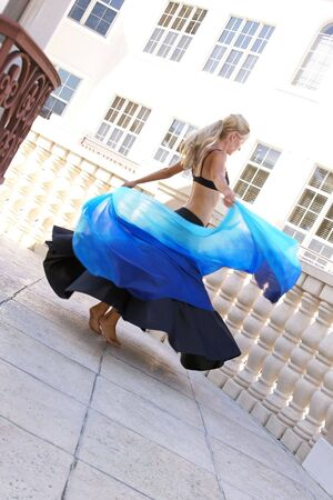 attractive blonde belly dancer spinning with veil outside on balcony photo