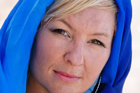 brown  eyed: a confident brown eyed woman with head slightly tilted is looking directly at viewer, she has blonde hair and her head is covered in a hood of silk Stock Photo