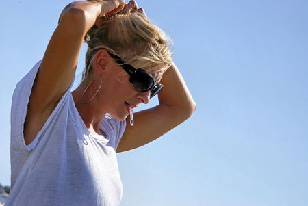 a beautiful blonde woman outsdie at the beach is fixing her hair, wearing sunglasses, large hoop earrrings and a shiny tee shirt with space for copy or text