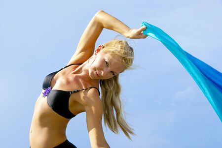outdoor portrait of attractive blonde belly dancer arching back making eye contact with the viewer against  powder blue sky photo