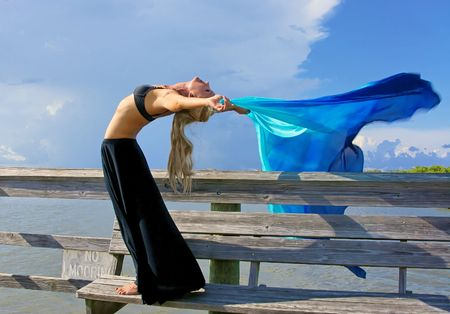 fit and attractive blonde woman is arching back making her arms horizontal as the wind blows back her veil