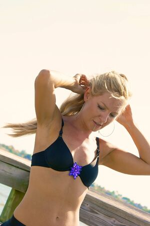 bobby: beautiful blonde woman fixing hair in bikini with bobby pins in her mouth, outdoors at beach