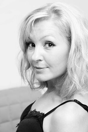perky: casual portrait of beautiful perky blonde woman in bra turning her head looking slightly surprised and happy. black and white image