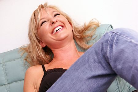 a beautiful young lady is sitting on sofa with her head back laughing Stock Photo - 5490653