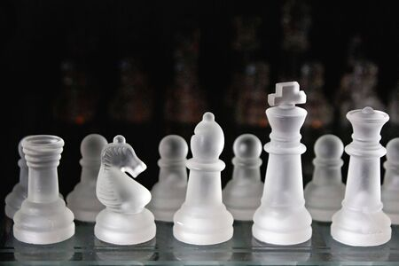 opponents: a frosted glass chess set on a glass chess board with a dark background, opponents chees men can be seen in the distance with plenty of room for copy or text