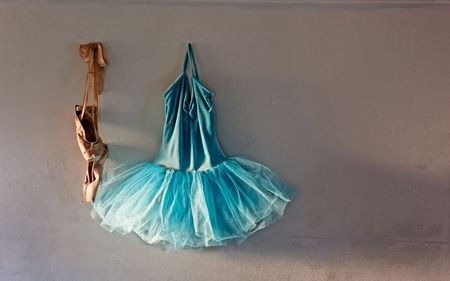 velvet dress: a blue velvet romantic tutu is hanging on a old wall in dressing room beside a worn pair of ballet pointe shoes with copy or text space, lit only by sunlight through window Stock Photo