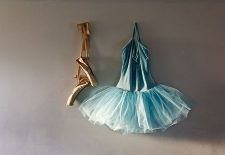 ballet shoes: a blue velvet romantic tutu is hanging on a wall beside a worn pair of ballet pointe shoes, lit only by sunlight through window Stock Photo