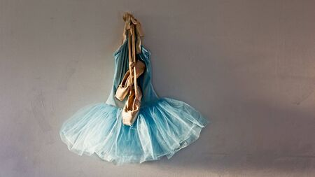 velvet dress: a blue velvet romantic tutu is hanging on a wall in dressing room with a worn pair of ballet pointe shoes on top of dress with copy or tesxt space, lit only by sunlight through window Stock Photo