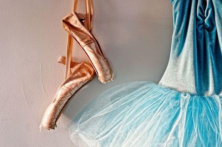 ブルー ベルベットのロマンチックなチュチュ バレエ ポワント シューズ、窓から日光に照らされてのみの着用のペアの側の壁にぶら下がっています