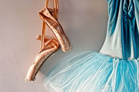 worn: a blue velvet romantic tutu is hanging on a wall beside a worn pair of ballet pointe shoes, lit only by sunlight through window Stock Photo
