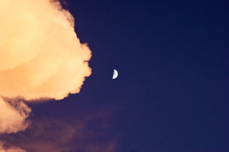 a large cloud lit by the setting sun is filling the frame from the left with a half moon in the center leaving the rest of the image with open sky Imagens - 5647004