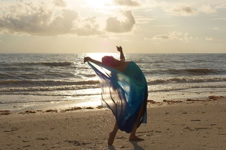 arching: an attractive fit blonde dancer is arching back on pointe at the beach in sheer flowing costume looking at you the viewer as the sun begins to set behind her
