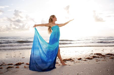 brightness: a female dancer is posing in profile with arms raised and looking at her open hand at the beach with brightness of the sun diffusing her hand Stock Photo