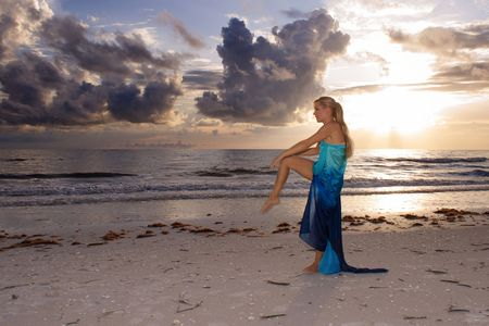 a woman is standing on the beach at sunset looking out into the ocean standing on one  leg doing a dance or yoga stretch. photo