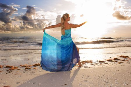 brightness: a beautiful blonde woman is standing with her back to the viewer with her hand up so that the brightness of the sun obscures her hand Stock Photo