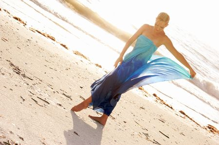 a woman is walking on the beach looking down and holding up the bottom of her dress in this soft dreamlike image.