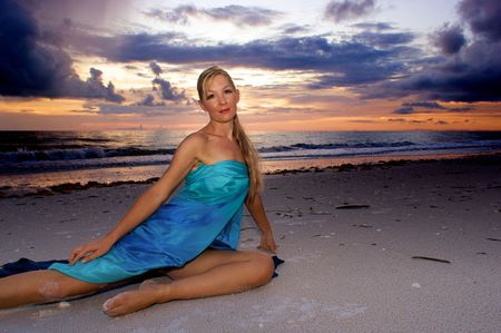 beach wrap: a beautiful blonde woman in a blue wrap is sitting on the beach in this tropical sunset scene with room for copy, useful as a travel ad, looking at the viewer