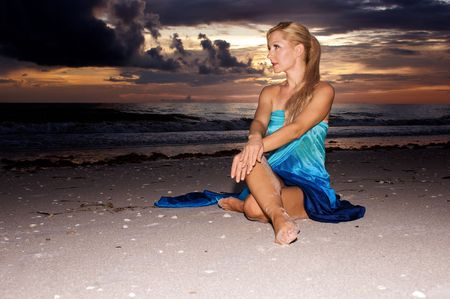 an attractive blonde woman with a ponytail is sitting on the beach at sunset, in profile with wrists crossed Stock Photo