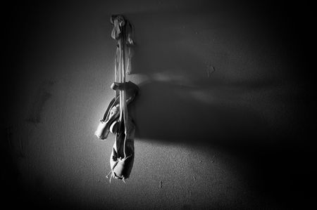 worn: A worn out pair of ballet pointe sose is hanging from a wall with dramatic lighting and lit from the left in this black and white image with plenty of copy space. Stock Photo