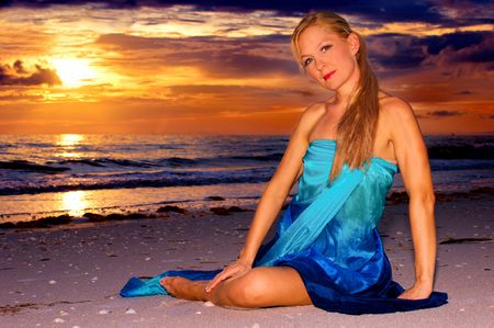 intensely: A beautiful woman is sitting on the beach infront of a beautiful intensely colorful sunset looking directly at you the viewer in this tropical feeling scene.