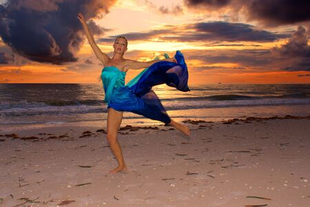 beach wrap: A blonde woman is dancing on beach in front of a fiery sunset with dark clouds.