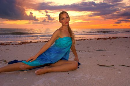 stretched out: A vibrant tropical sunset over the ocean with an attractive blonde haired woman stretched out on the beach looking directly at viewer. Stock Photo