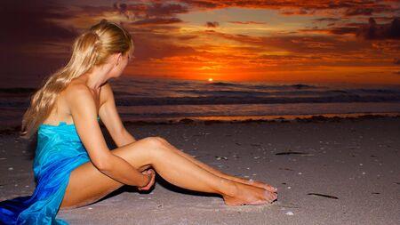 knees bent: una lunga donna dai capelli biondi � seduto sulla spiaggia guardando lontano verso il sole al tramonto, con copia spazio.