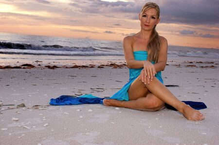 woman sitting cross legged on beach looking directly at the viewer, her legs are crossed and her hands are resting on her knees. with copy space.
