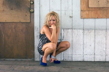 squatting down: A beautiful blonde woman in a short dress, is squatting down, smiling as she looks at the ground in front of an old door and old wall