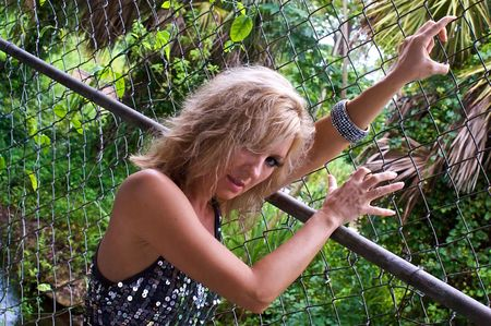A beautiful blonde woman is holding  a chain link fence and looking like she is climbing it, looking back over her shoulder at the viewer, wearing a silver sequined dress with trees in the background. photo