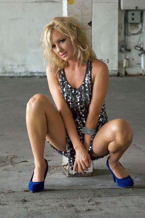 An attractive blonde woman in a silver sequined short dress and blue suede shoes is squatting down with her hands crossed between her open legs with her body turned towards viewer..