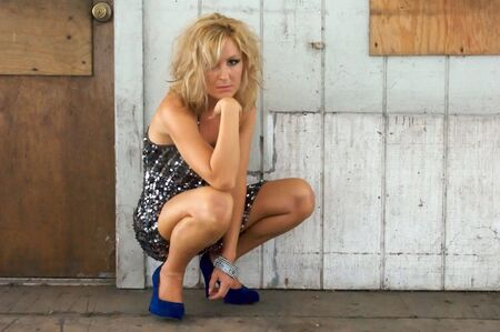 grubby: A beautiful high class blonde woman is squatting down in grubby surroundings straing at viewer with a blank expression on her face. Stock Photo