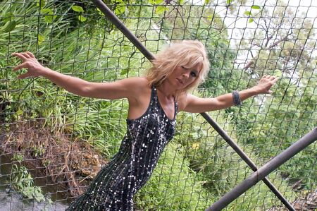 clinging: A slim attractive woman in heavy make up and party dress is clinging onto a chain link fence with trees in the background. Stock Photo