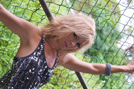evening out: A pretty blonde woman dressed for an evening out is leaning against a chain link fence with her arms out stretched and looking at the viewer.