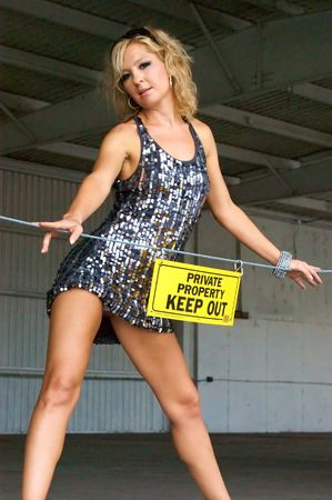 A pretty blonde wearing a short dress has her hip pushed out and is looking down at viewer from loading dock behind a sign that reads