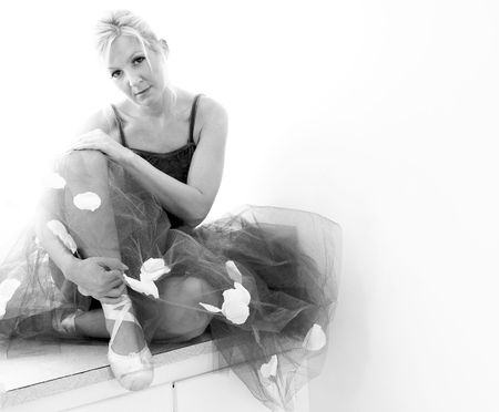 A beautiful blonde ballerina is sitting with her legs crossed holding her ankle and looking at the viewer in this high key black and white image.