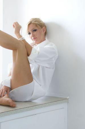 A beautiful blonde lady is sitting on a window seat wearing only a man's white dress shirt as she looks at the viewer, her leg is raised. Stock Photo - 5841205