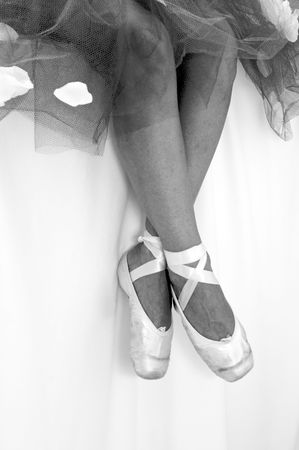 black and white image of a ballerinas feet showing pointe shoes, her ankles are crossed. Stock Photo