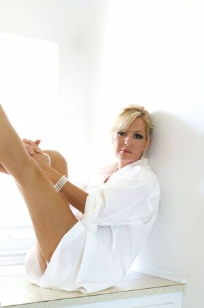 An attractive blonde woman is sitting in the morning sun wearing only a man's white dress shirt, with her legs up looking at the viewer.