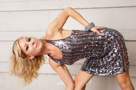 stage make up: A beautiful blonde model in metallic looking dress is bending over sideways looking at viewer. Stock Photo