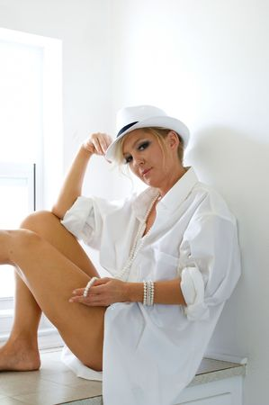 A beautiful woman is sitting on a window seat wearing only a mans hat and dress shirt, looking at viewer. photo