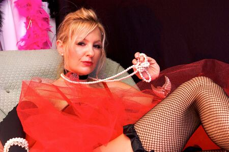 moll: Beautiful blonde laying on chaise loungelooking at viewer with a knowing look on her face. Actress dressed up as old fashioned madam or prostitute can also be a sexy mrs. claus or santas elf for christmas. Enhanced with blue and red colored strobes to ad