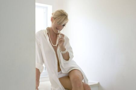 blond brown: An attractive semi nude woman is sitting with her shirt open and wearing white panties as she looks at viewer with a string of pearls in her mouth.