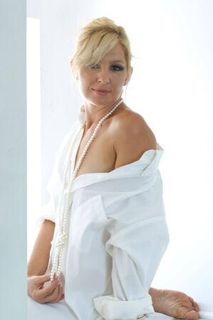 off shoulder: An attractive blonde woman is wearing a mans dress shirt and her shoulder is exposed. Stock Photo