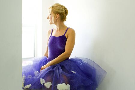 velvet dress: Adult ballerina wearing purple tutu is turned in profile and looking out window.