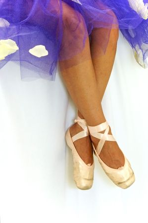 View of ballerinas legs and feet, wearing a purple tutu and ballet slippers. Stock Photo