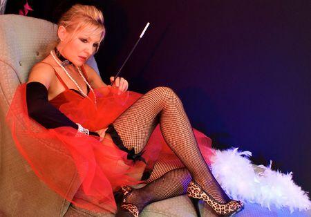 medias de red: Ver todo el cuerpo de la bella rubia por el div�n. La actriz disfrazada de se�ora pasada de moda o prostituta tambi�n puede ser una se�ora sexy. Claus o los elfos de Santa Claus para Navidad. Tiro con luces estrobosc�picas azul y rojo. Foto de archivo