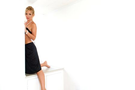An attractive blonde woman half kneeling in a white room ileaning on wall n black bra and slip looking at viewer.